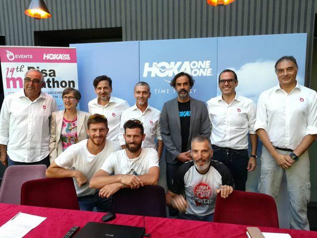 Alcuni esponenti di AD 1063, società organizzatrice dell'evento pisano in compagnia di Alessio Ranallo, in grigio, responsabile di Hoka One One e alcuni atleti Hoka accosciati