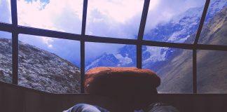 Dormire bene - Nella suggestiva immagine della fotografa Maeghan Smulders una ragazza dorme serena. Le montagne sullo sfondo la attendono per una nuova escursione giornaliera. Il Sole è già alto ed è ora di svegliarsi!